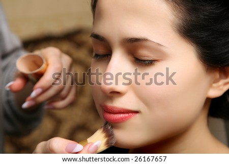 makeup artist applying lipstick on the lips of a beautiful young woman - stock photo