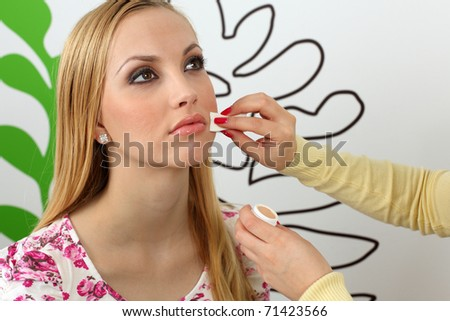 Makeup artist applying makeup on attractive young woman face. - stock photo