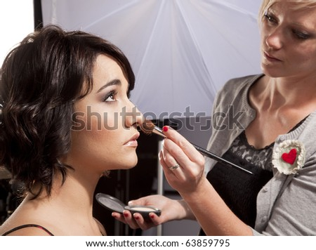 Makeup artist applying makeup to a model at a photo shoot. - stock photo