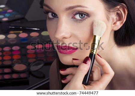 Makeup artist applying shimmer powder on woman face