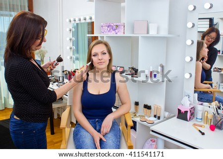 Makeup artist at work on attractive woman in salon - stock photo