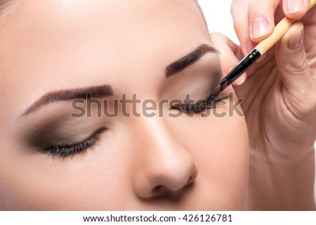 makeup artist deals makeup brush for eyes. makeup for a young beautiful girl. brown eye shadow.