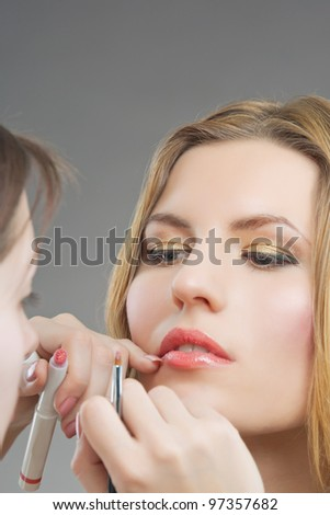 makeup artist doing lips makeup with a brush to young blonde woman