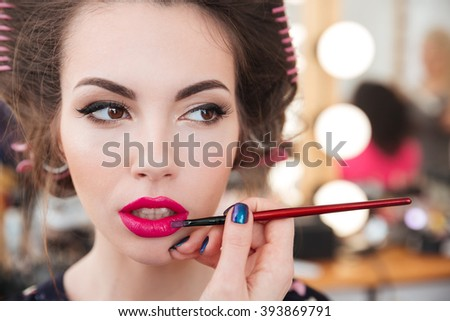 Makeup artist doing makeup and applying bright pink lipstick using brush in beauty salon - stock photo