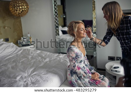 makeup artist doing  makeup for the beautiful  bride in her home