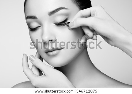 Makeup artist glues eyelashes. Beautiful woman face. Perfect makeup. Beauty fashion. Eyelashes. Cosmetic Eyeshadow - stock photo