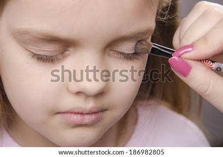 Makeup artist in the process of makeup colors eyelids on the face five year old girl