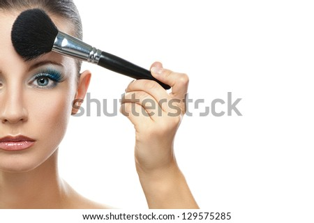Makeup artist prepares forehead beautiful dark-haired woman, isolated on white background. - stock photo