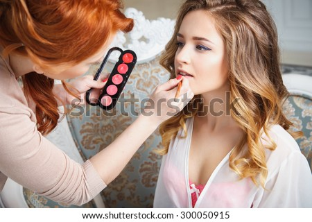 makeup artist preparing bride before the wedding in a morning - stock photo