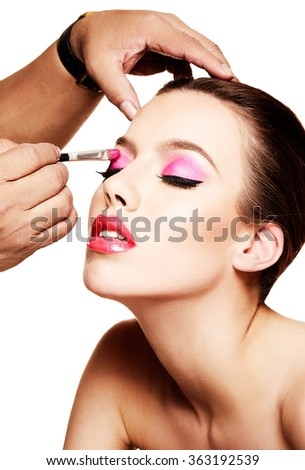 Makeup artist putting pink eye shadow on the beautiful woman. Isolated on white.  - stock photo