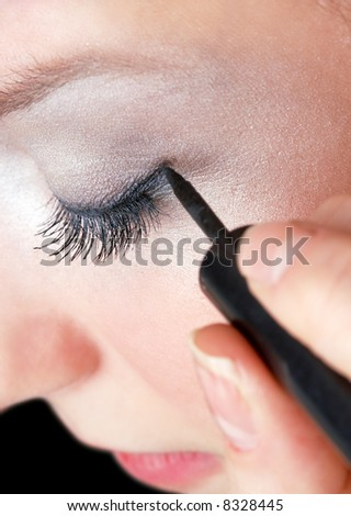 makeup artist tracing eye line with black eyeliner, beautiful girl - stock photo