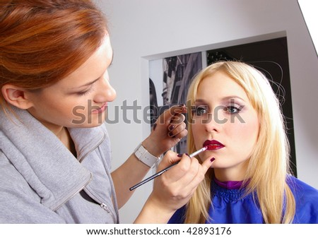 Makeup artist tracing red lipstick on the lips of a girl - stock photo