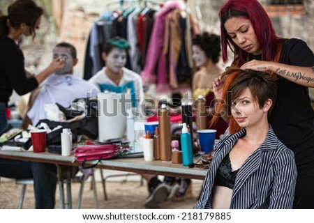 Makeup artist with red hair fixing young woman's hairdo - stock photo