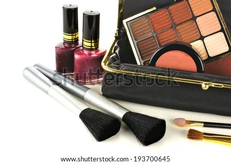 Makeup bag close up with assorted cosmetics over a white background            - stock photo