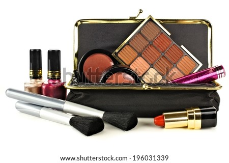 Makeup bag with assorted beige hue cosmetics on a white background - stock photo