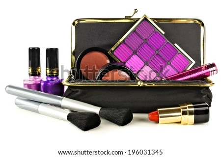 Makeup bag with assorted purple hue cosmetics on a white background - stock photo