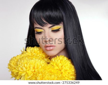 Makeup. Beautiful model brunette with long straight glossy hair and Yellow Eyeshadow with eyeliner with bright flowers.  - stock photo