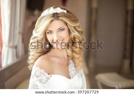 Makeup. Beautiful smiling Bride wedding Portrait with wedding hairstyle, Wedding dress. Wedding decoration. soft selective focus. gorgeous young woman at home - stock photo