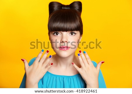 Makeup. Beautiful teen girl with bow hairstyle and multicolor manicured polish nails. Funny girl showing ten fingers isolated on studio yellow background. - stock photo