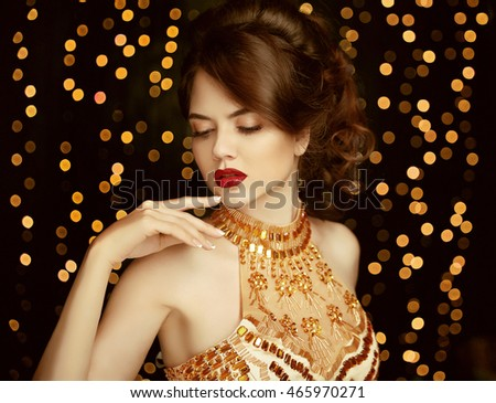 Makeup. Beautiful Young Woman in fashion golden dress. gorgeous girl. Vogue style. Elegant lady on party. Fashion model  isolated on Christmas party lights background.