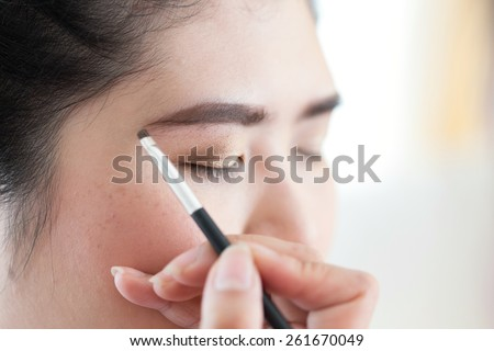 makeup beauty with brush eyebrow on pretty woman - stock photo