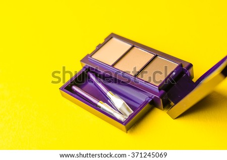 makeup brush and cosmetic powder close. Top view on a yellow background