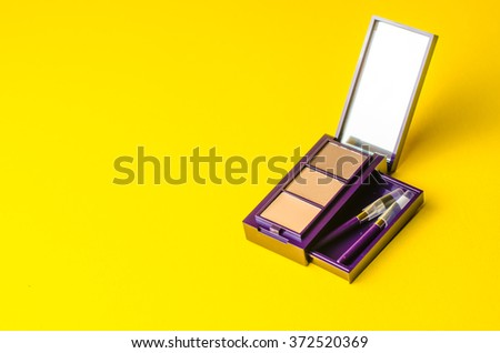 makeup brush and cosmetic powder close. Top view on a yellow background - stock photo