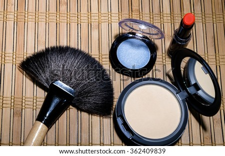 Makeup brush and cosmetics on the wooden floor . - stock photo