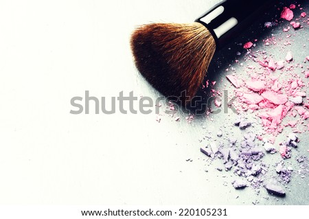 Makeup brush and crushed eyeshadows on light background - stock photo