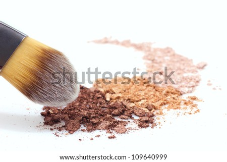 makeup brush and multicolored eyeshadow on white background - stock photo