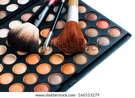 Makeup brushes and eyeshadow palette in beige and orange tones, cosmetics isolated close-up - stock photo