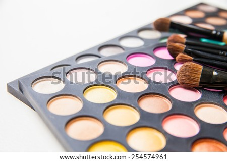 Makeup brushes and make-up eye shadows isolated over white background - stock photo