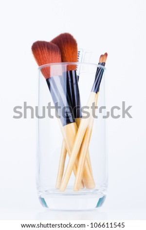Makeup brushes in a glass of water - stock photo