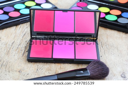 Makeup brushes make-up eye shadows vintage wooden background - stock photo