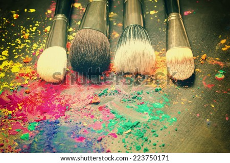 Makeup brushes on background with colorful powder. Make-up background  - stock photo