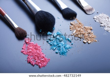 Makeup brushes on black background with colorful powder macro. Make-up background