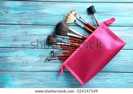 Makeup brushes set on a blue wooden background - stock photo