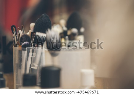 Makeup brushes stand in a transparent glass shot with blur background in retro colours