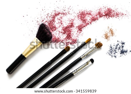 Makeup brushes with blusher and eyeshadow sample on white background - stock photo