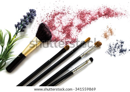 Makeup brushes with blusher and eyeshadow sample on white background. Woman's Day. March 8. - stock photo