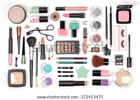 makeup cosmetics, brushes and other essentials on white background top view. beauty flat lay concept in pink and green colors - stock photo