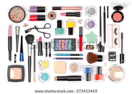 makeup cosmetics, brushes and other essentials on white background top view. multicolored beauty flat lay concept - stock photo