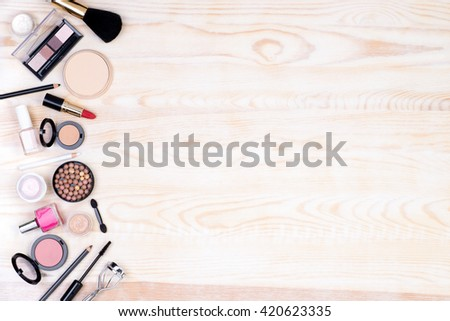 Makeup cosmetics on white, wooden background with copy space, top view - stock photo