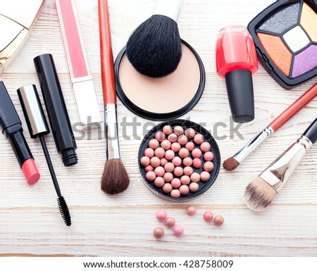 Makeup cosmetics products on white wooden background with copy space. Cosmetics make up artist objects: lipstick, eye shadows, eyeliner, nail polish, powder, tools for make-up. Selective focus