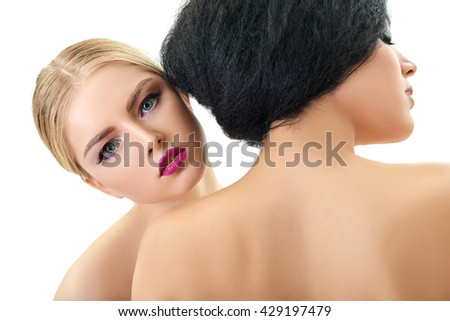 Makeup. Double female portrait. Caucasian blond girl and beautiful mulatto young woman posing in studio over white background. Fashion, beauty, glam, youth. - stock photo
