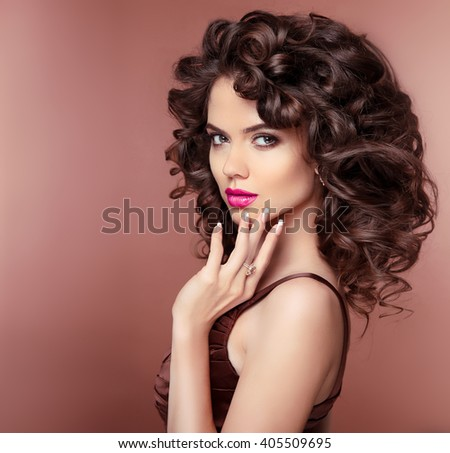 Makeup. Hair. Attractive brunette girl with healthy curly hairstyle and pink lips, manicured nails. Fashion Jewelry. - stock photo