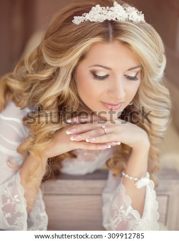 Makeup. Hair. Beautiful smiling girl bride with long blonde curly hairstyle and bridal makeup. Wedding indoor portrait. - stock photo