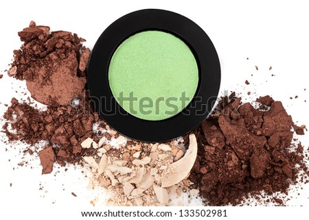 Makeup in natural brown and green color tones. Crushed and spilled facial powder and eyeshadow isolated on white background, top view. Luxurious cosmetic background.