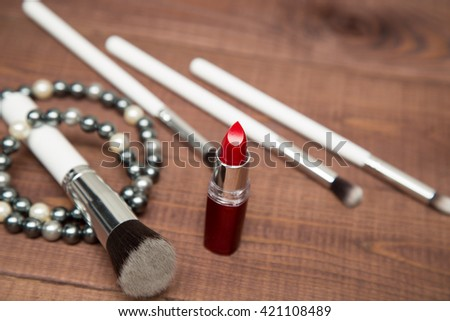 makeup items - white brushes and red lipstick, scattered across a wooden surface