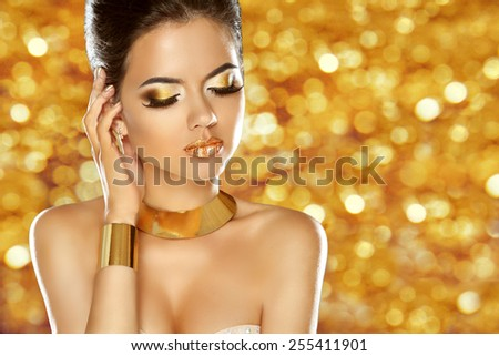 Makeup. Jewelry. Glam lady. Beauty fashion girl model isolated over sparkling golden background. - stock photo